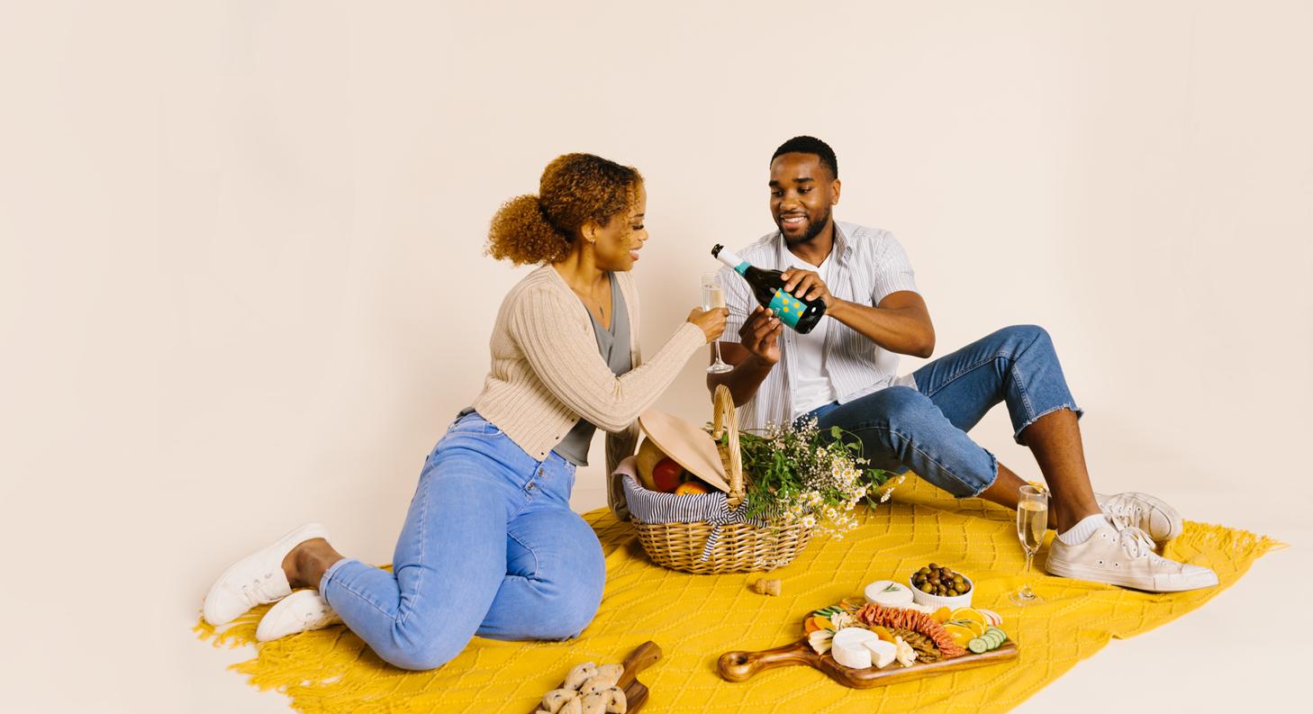 couple enjoying picnic with coda prosseco