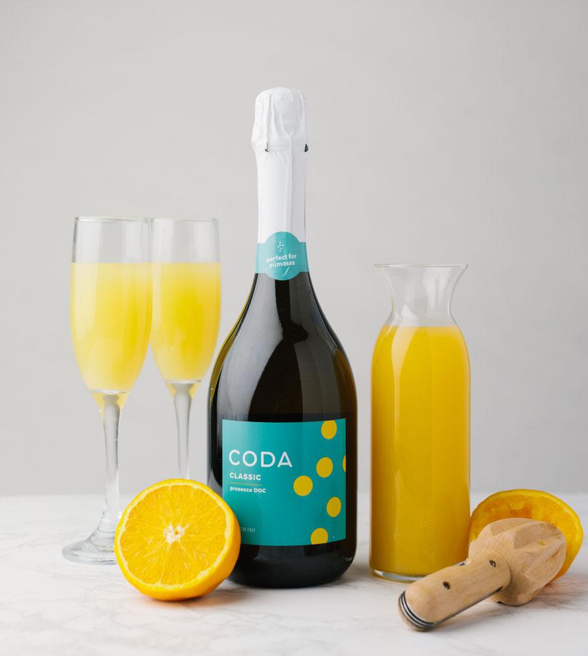 coda classic bottle surrounded by mimosas, orange juice, oranges, and juicer
