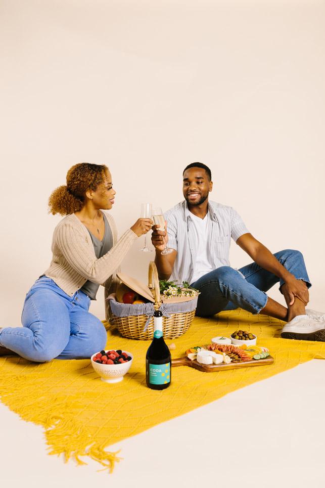 couple enjoying picnic with snacks and clinking glasses of coda