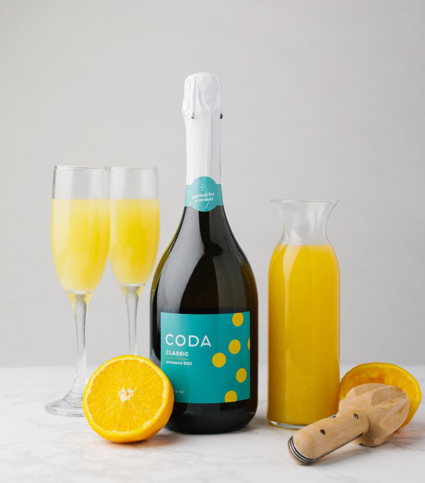 bottle of Coda Classic with two glasses of mimosas, orange juice, orange, and juicer