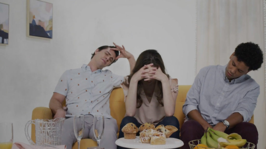 group of young adults on couch holding their heads with hangovers