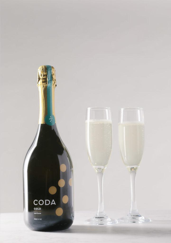 bottle of coda gold next to two full glasses